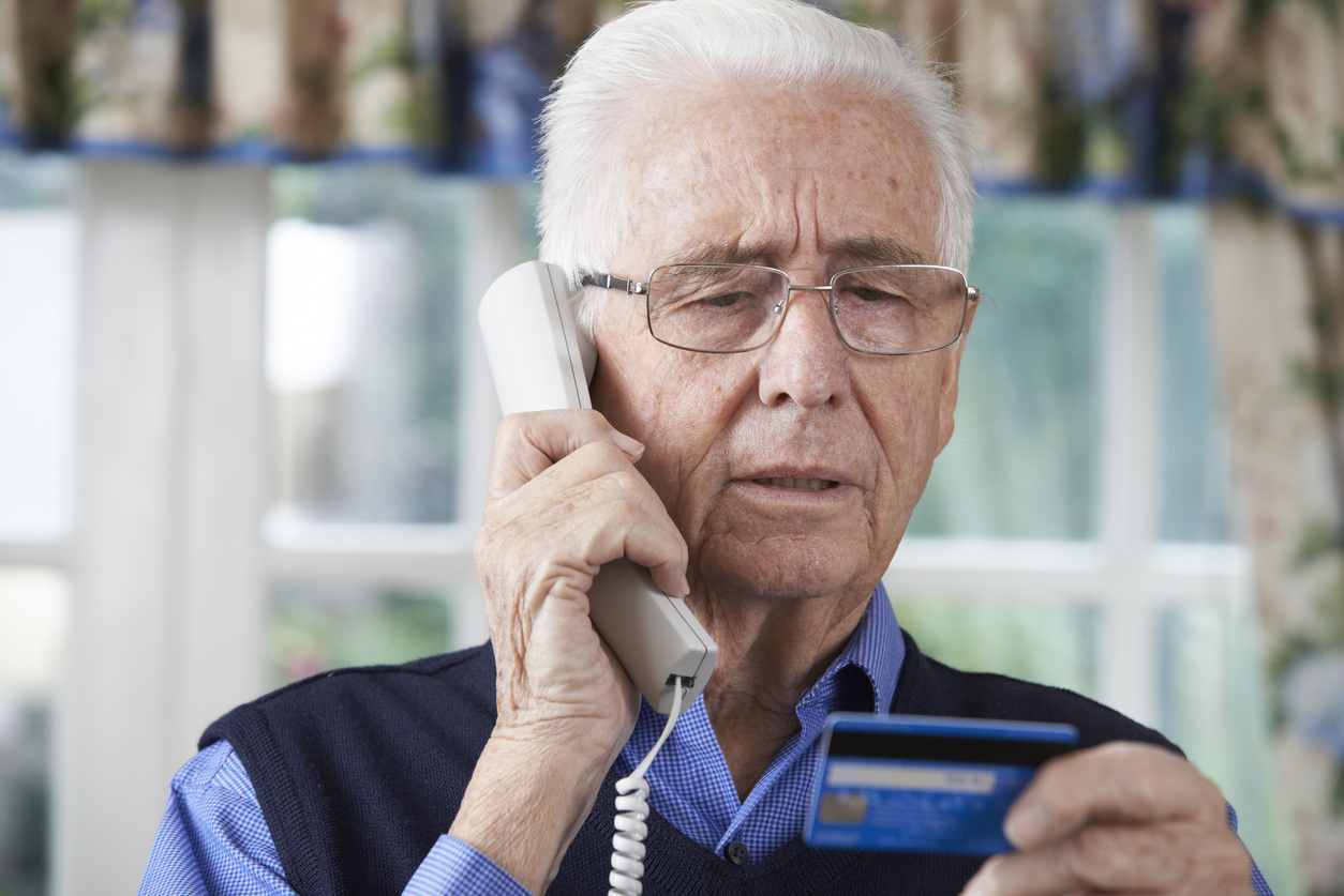 Elderly man on the phone reading his credit card details